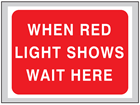 When red light shows wait here roll up road sign