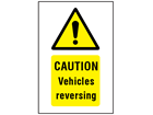 Caution Vehicles reversing symbol and text safety sign.