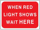 When red light shows wait here temporary road sign.