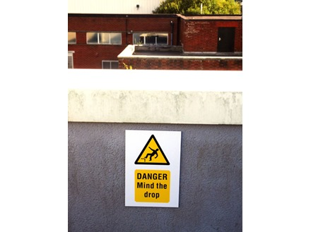 Caution, Mind the drop symbol and text safety sign.