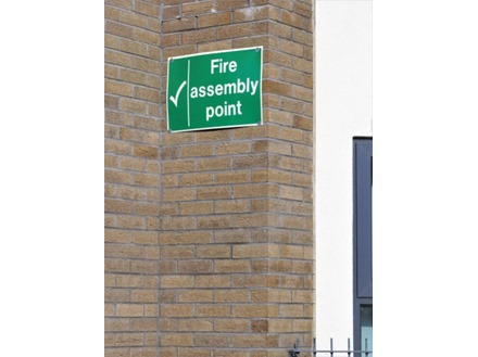 Fire assembly point text safety sign.