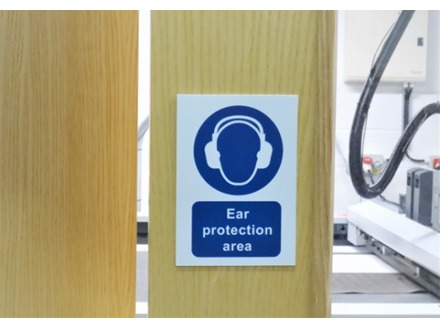 Ear protection area symbol and text safety sign.