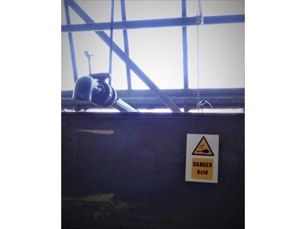 Danger acid symbol and text safety sign.
